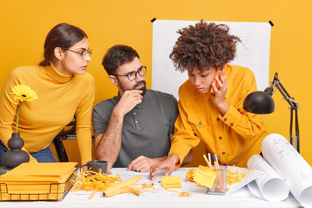 Team od mixed race two women and one man try to create new strategies try to solve problems while doing sketches of future building. afro american woman calls partnes via smartphone asks for advice