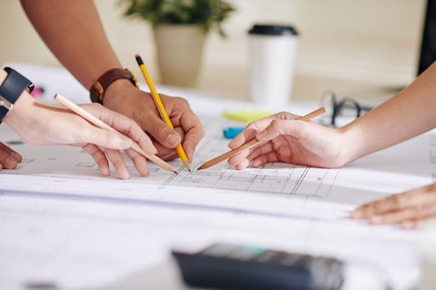 建築家とエンジニアのチームが建物の建設計画を指しています