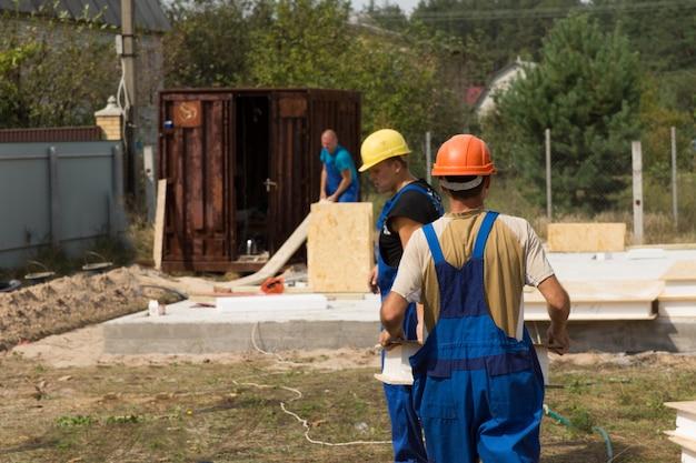 단열된 목재 벽 패널을 설치하는 신축 주택 건설 현장의 건축업자 또는 작업자 팀
