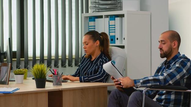 新しいプロジェクトを計画しているビジネスマンのチーム、ドキュメントからの財務データを同僚と比較する車椅子の麻痺したマネージャー。現代の技術を使用して障害者、動けないビジネスマン