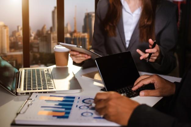 스마트폰과 태블릿을 개념으로 사용하여 현대의 비즈니스 전략을 논의하는 비즈니스 분석가 팀