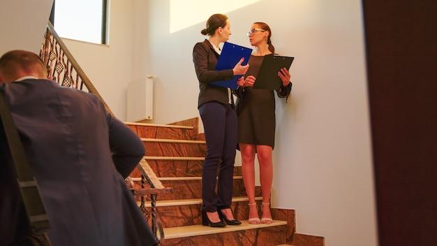 ビジネスマンとマネージャーの幹部のチームが立って階段を歩いて、クリップボードを持って話します。現代の金融ビルで働くプロの成功したビジネスマンのグループ。