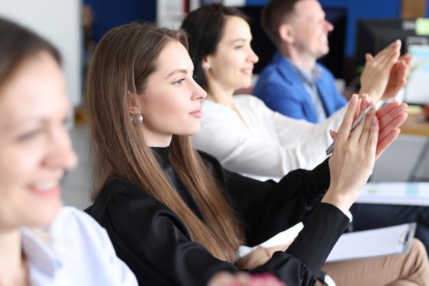Команда деловых людей аплодирует на семинаре