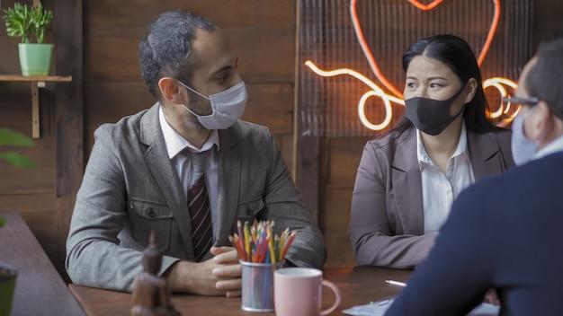 コロナウイルスの発生中、ビジネスマンのチームはチームワークで忙しい。