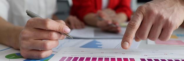 ビジネスマンのチームは、オフィスのクローズアップパートナーシップの概念で財務チャートを研究しています
