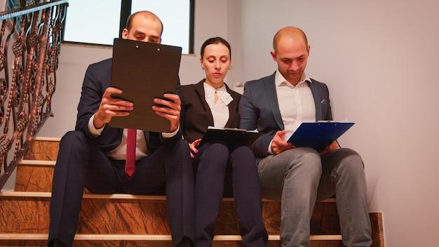 財務プロジェクトを説明する階段に座って楽しんで年次グラフを分析する計画を立てるビジネスマンのチーム。職場の忙しい階段で会社のマネージャーとオフィスエグゼクティブのグループ。