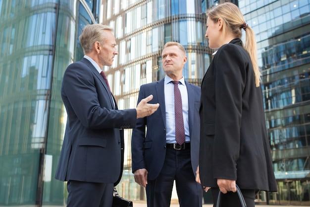 비즈니스 사람들이 도시에서 회의, 서서 사무실 건물에서 이야기, 계약을 논의하는 팀. 낮은 각도 촬영.