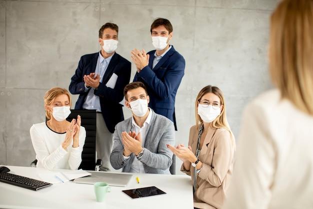 Команда деловых людей работает над проектом с масками для лица в качестве защиты от вирусов в офисе
