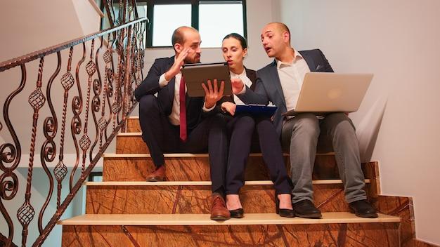 ノートパソコンとタブレットを使用して、財務プロジェクトを説明する階段に座って楽しんで、仕事の計画を立てるビジネスワーカーのチーム。忙しい階段で会社のマネージャーとオフィスエグゼクティブのグループ