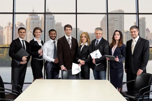 Команда бизнесменов в бизнес-центре. деловые люди на фоне города. деловая встреча.