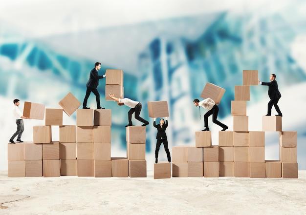 ビジネスマンのチームは、木製の立方体で構造を構築します
