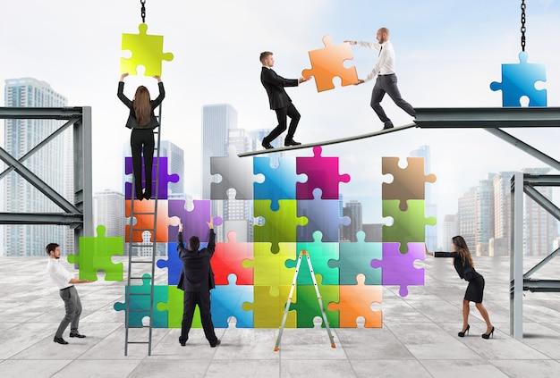 Команда бизнесменов строит пазл-конструкцию