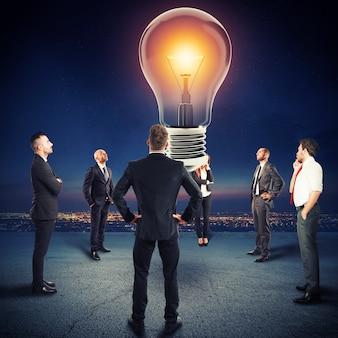 ビジネスマンのチームは大きな電球を見ます