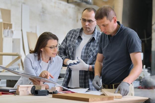 Бригада рабочих столярной мастерской обсуждает мебельный проект