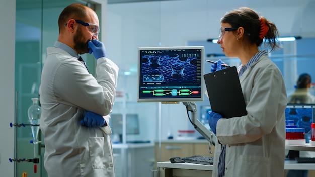 Dna 스캔 이미지로 작업하는 화학자 팀은 의학 연구 실험실에 서 있는 데스크탑을 보고 생화학 샘플을 분석하고 이야기합니다. 첨단 장비를 이용한 미생물 개발