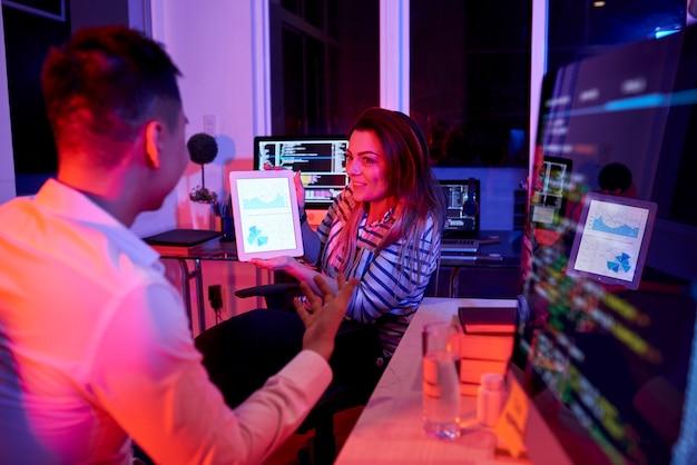 Команда кодеров обсуждает отчеты и статистику при работе в офисе поздно ночью