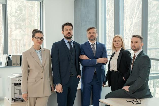 Команда уверенных в себе юристов в костюмах, стоящих вместе в офисе и смотрящих в камеру