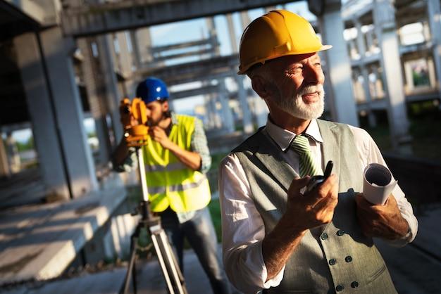 Команда инженеров-строителей и архитекторов, работающих на строительной площадке