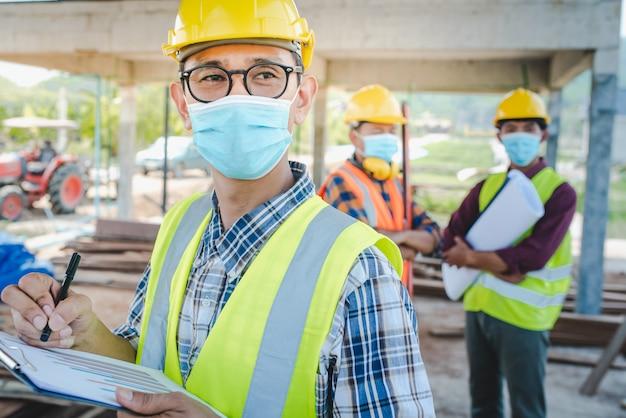建設エンジニアと3人の建築家のチームが医療用マスクを着用する準備ができています。 coronaまたはcovid-19は、建設の設計時にマスクを着用します。