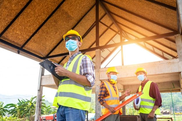 建設エンジニアと3人の建築家のチームが医療用マスクを着用する準備ができています