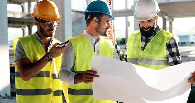 Команда инженеров-строителей, работающих на строительной площадке вместе