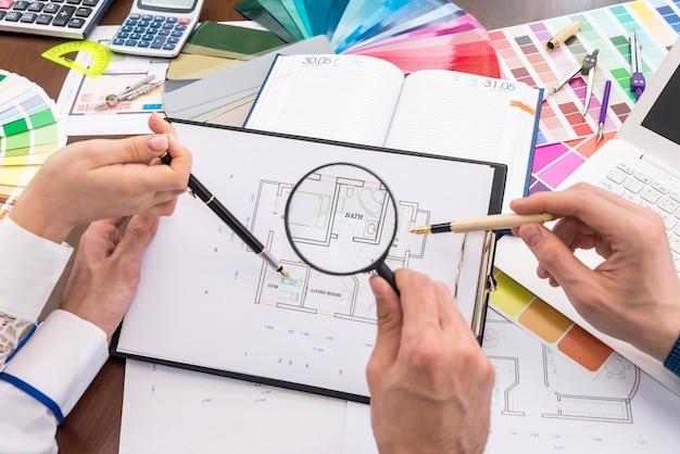 Команда креативных дизайнеров обсуждает план дома в офисе