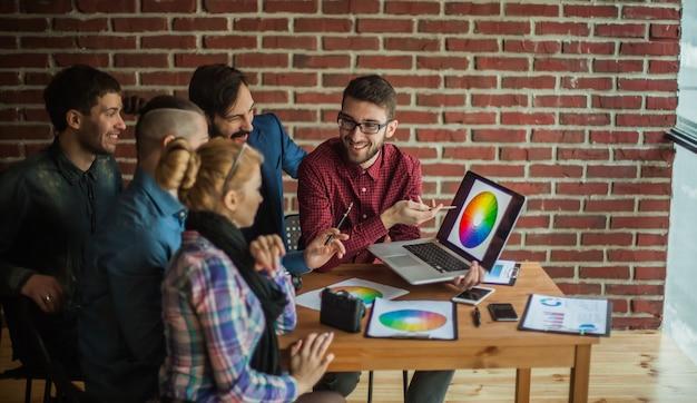 열린 노트북 앞에서 직장의 디자이너 팀이 새로운 색상 팔레트에 대해 논의하고 있습니다.