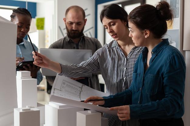 Команда разных архитекторов обсуждает чертежи планов на бумаге портативный компьютер планшетный профессионал