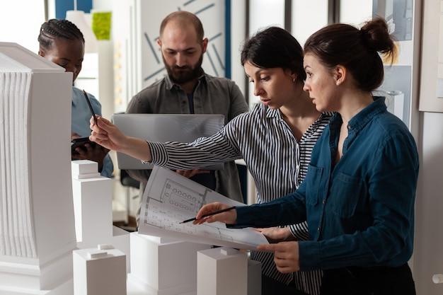 Команда разных архитекторов обсуждает планы проектов
