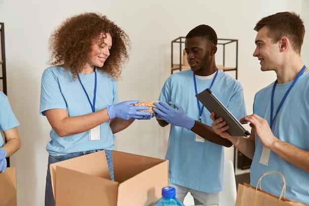식품 포장을 분류하는 동안 웃고 있는 보호 장갑을 낀 다양한 젊은 자원 봉사자 팀