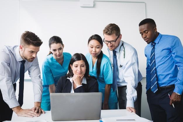 회의에서 노트북을 통해 논의하는 의사의 팀