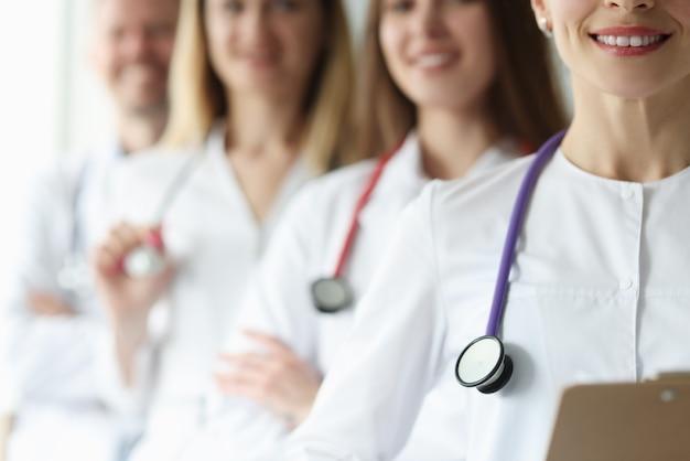 白衣と聴診器の医師のチームが一緒に立っています