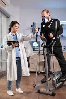 의사 연구원 팀은 크로스 트레이너를 실행하는 마스크를 착용한 남자 퍼포먼스 스포츠의 지구력을 모니터링합니다. 스포츠맨의 vo2를 측정하는 실험실 과학 의사는 건강 상태를 설명하는 엑스레이를 보고 있습니다.