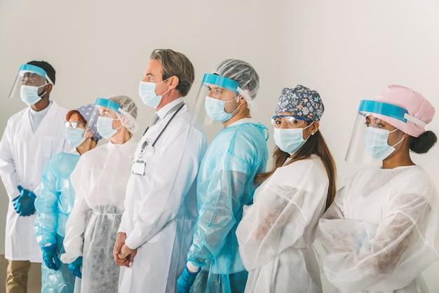 Covid19와 싸우기 위해 일회용 보호 복과 안면 마스크를 착용 한 의사와 간호사 팀