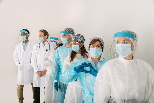 Covid19と戦うための使い捨ての防護服とフェイスマスクを身に着けている医師と看護師のチーム