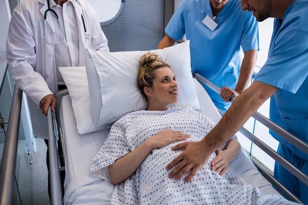 Команда врачей осматривает беременную женщину