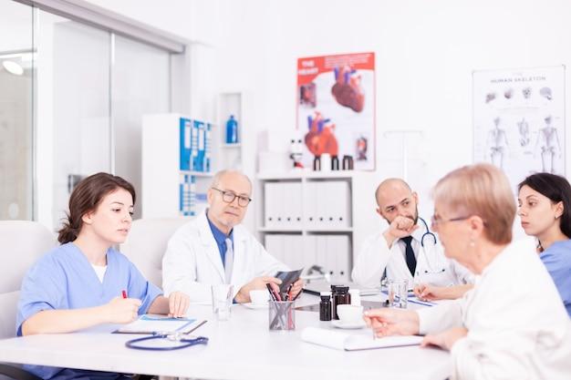 병원 회의실 책상에 앉아 브레인스토밍 세션을 하는 의사 팀. 질병에 대해 동료와 이야기하는 클리닉 전문 치료사, 의학 전문가