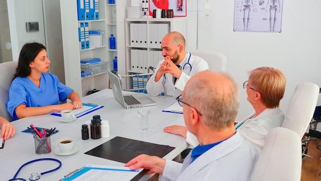 병원 회의실 책상에 앉아 브레인스토밍 세션을 하는 의사 팀. 병원에서 동료들과 질병, 질병의 증상에 대해 이야기하는 클리닉 전문 치료사