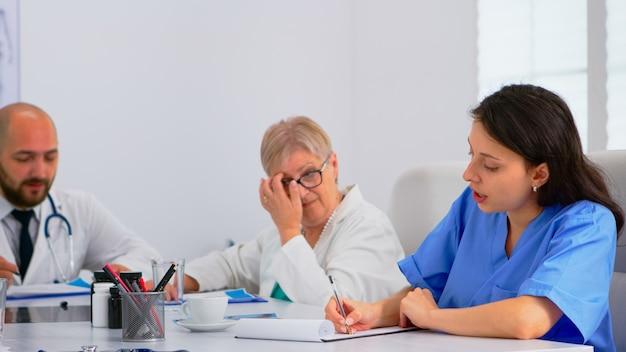 의료 회의를 하는 의사 팀은 업무를 나누고 병원 회의 사무실의 책상에 앉아 있는 환자 문제에 대해 논의합니다. 질병의 증상에 대해 이야기하는 의사 그룹