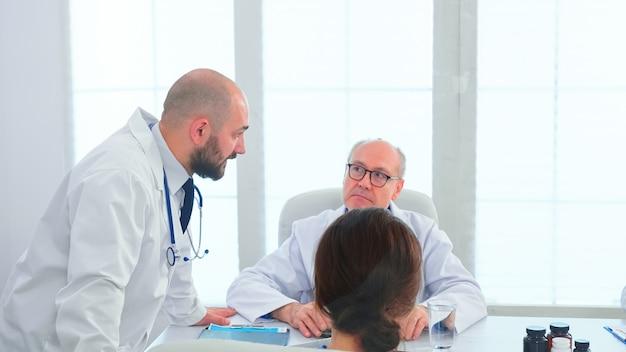 병원 회의실에서 진단을 설정하는 병원 사무실의 의사 팀. 질병에 대해 동료와 이야기하는 클리닉 전문 치료사, 회의실에서 일하는 의학 전문가
