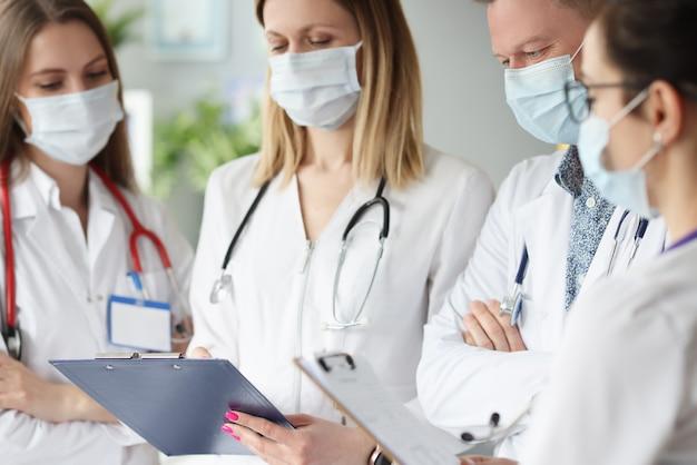 健康診断の結果を調べる医療用保護マスクの医師のチーム