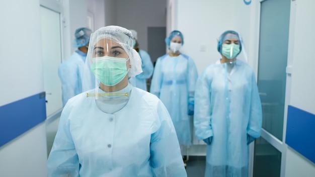보호 복을 입은 의사 팀. 의료 노동자들이 현대 병원의 복도를 걸어 내려갑니다. 코로나 19 퇴치. 클리닉의 의사