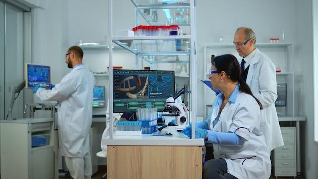 顕微鏡下でサンプルを見ている近代的な設備の整った実験室でコロナウイルスに対するワクチンを革新する医師のチーム。研究のためにハイテクを使用して治療の進化を調べる多民族チーム。