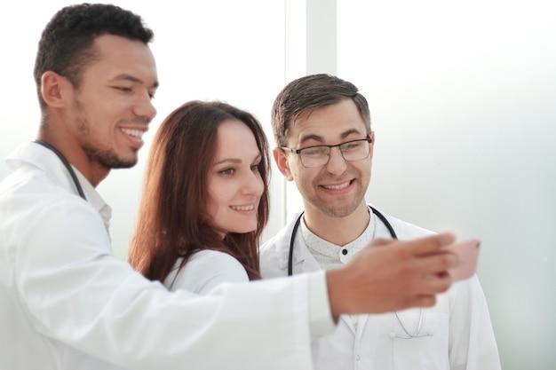 病院のロビーで自分撮りをしている医師のインターンのチーム。コピースペースのある写真