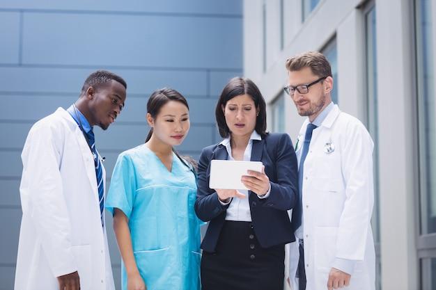 Команда врачей, глядя на цифровой планшет
