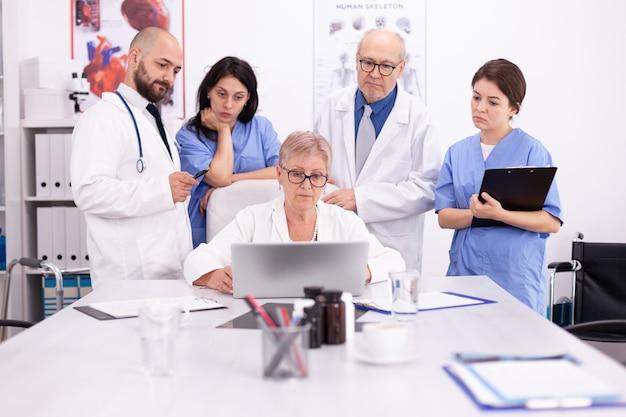 의료 유니폼을 입고 회의실에서 노트북을 보고 있는 의사 팀. 질병에 대해 동료와 이야기하는 클리닉 전문 치료사, 의학 전문가