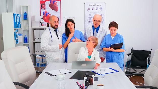 회의실에서 의료 유니폼을 입고 회의실에서 노트북을 보고 있는 의사 팀. 질병에 대해 동료와 이야기하는 클리닉 전문 치료사, 의학 전문가