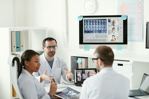 테이블에 앉아 동료들과 온라인 회의 중에 엑스레이 이미지를 함께 논의하는 의사 팀