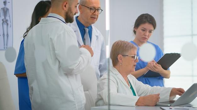 Команда врачей, стоя в конференц-больничной палате, старший врач обсуждает лечение пациента, смотрящего в ноутбук. коллеги в белых халатах вместе анализируют симптомы болезни