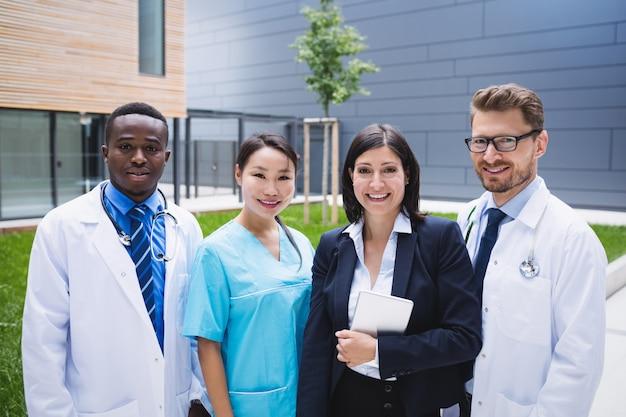 병원 구내에 함께 서있는 의사 팀
